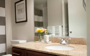 Center City apartment bathroom with designer storage vanity and granite top